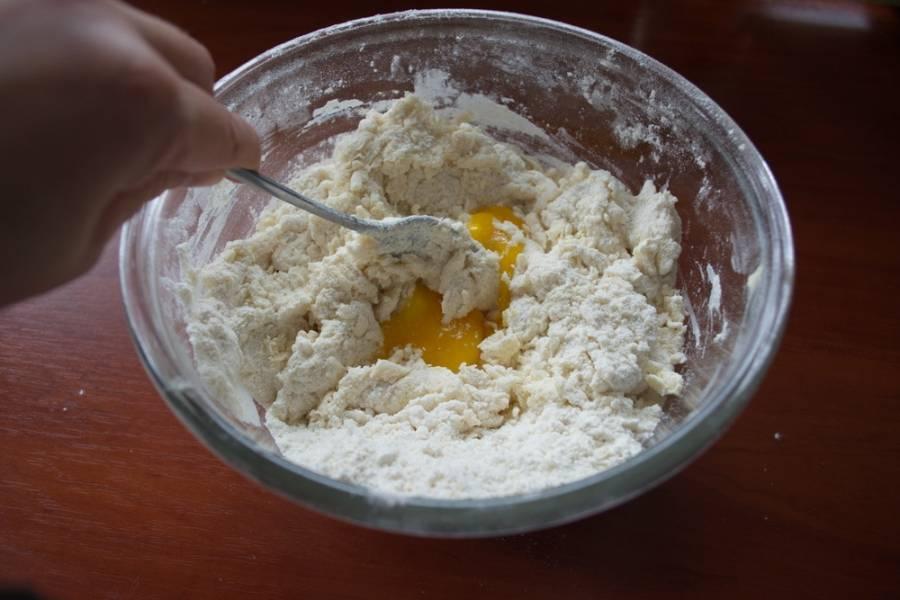 В полученную крошку добавляем яйцо и кефир. Замешиваем миксером тесто.