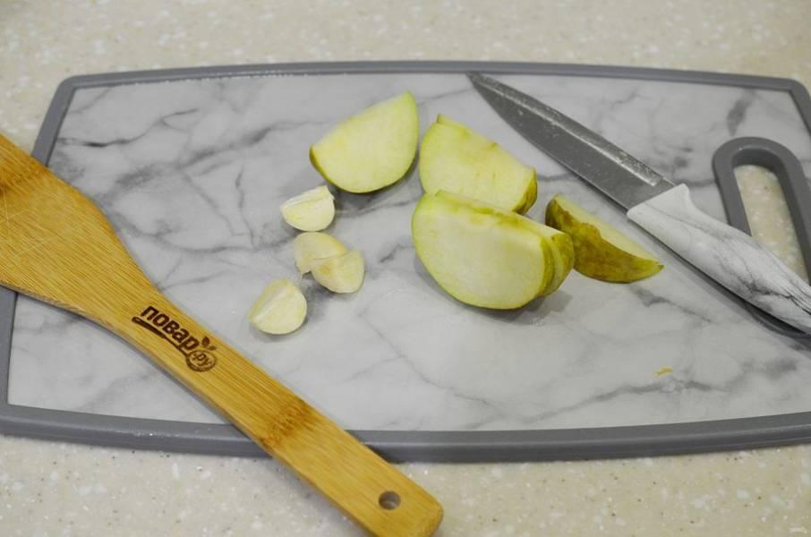 5. Яблоко нарежьте дольками, чеснок почистите. Начините курицу.