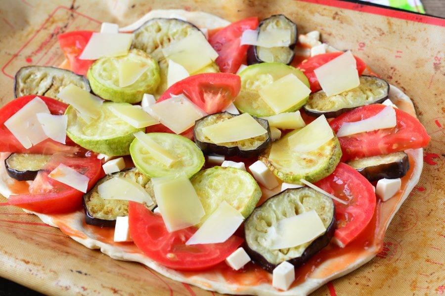 Выложите помидоры, жареные баклажаны и кабачки. Добавьте слайсы твердого сыра, у меня был пармезан.