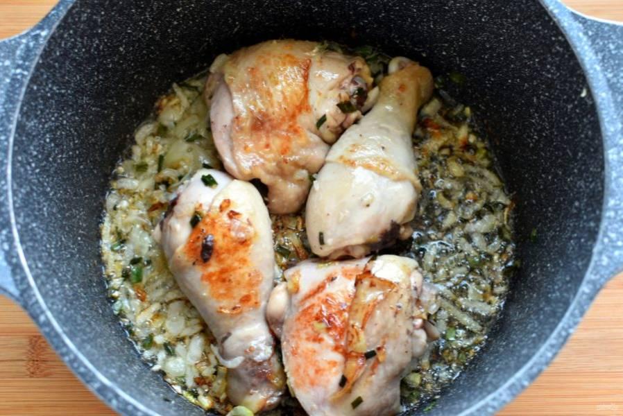Выложите сверху разрезанные пополам окорочка и обжарьте до румяной корочки. Выньте окорочка на тарелку и всыпьте к луку промытый и обсушенный рис. Обжаривайте 3-4 минуты, помешивая.