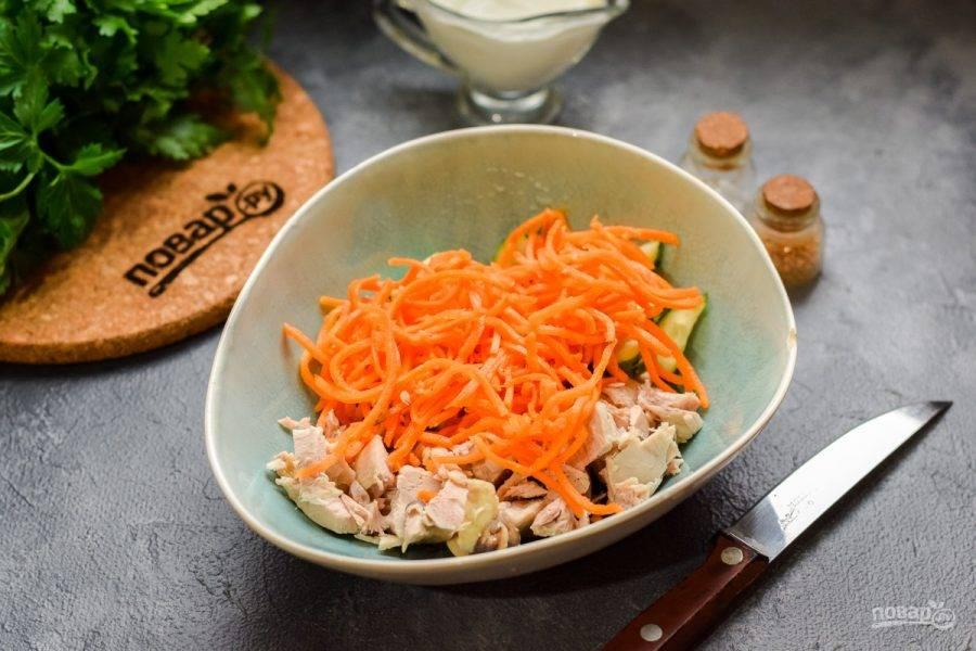 Переложите курицу и огурец в салатник. Добавьте в салат морковь по-корейски. Если она сильно длинная, нарежьте ее небольшими кусочками.