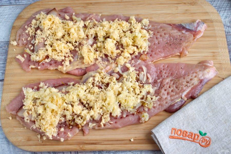 Выложите сверху поджаренный лук и бекон, посыпьте тертым сыром.
