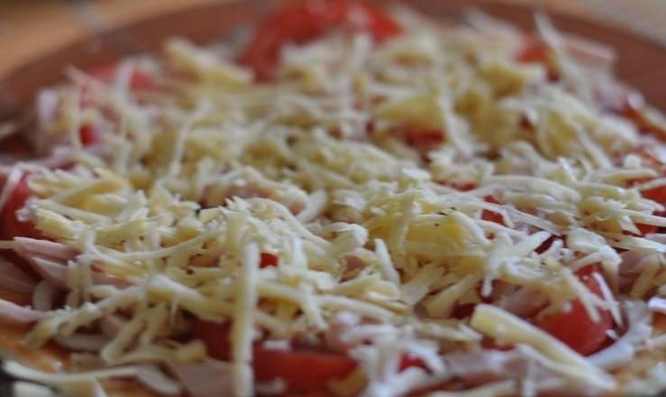Затем выложить начинку, нарезанную на кружочки, кольца, кусочки, равномерно распределить. Посыпать натёртым сыром. Можно использовать любой хорошо плавящийся твёрдый сыр или моцареллу или вообще обойтись без сыра, поскольку начинка при таком способе запекания остаётся сочной и без сырной корочки.