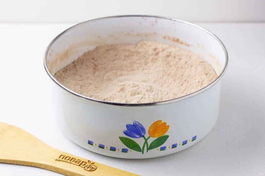 Смешайте все сухие ингредиенты для бисквита: просеянную муку, стакан сахара, какао-порошок, разрыхлитель, соду.