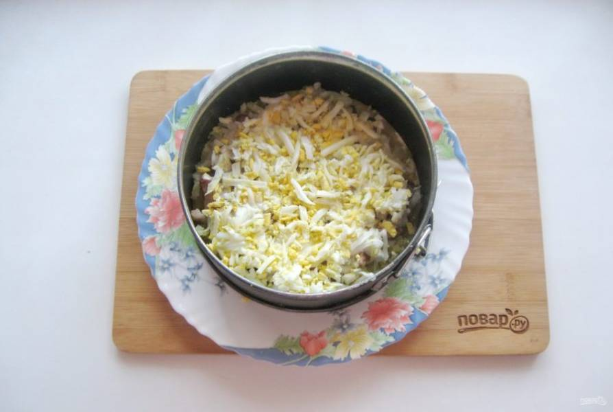 Яйца сварите вкрутую. Охладите и очистите. Натрите на терке и выложите на слой лука. Смажьте майонезом.
