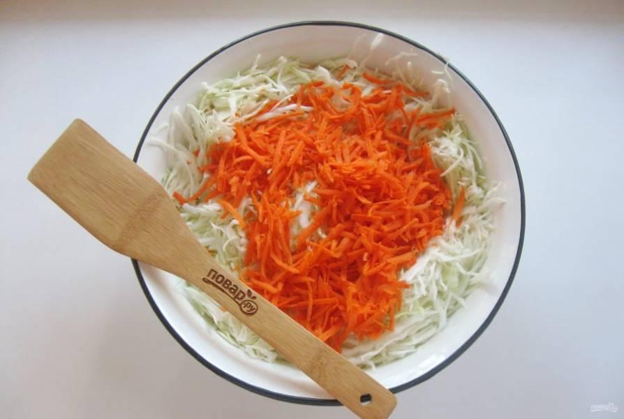 Морковь очистите, помойте и натрите на терке. Добавьте в капусту.