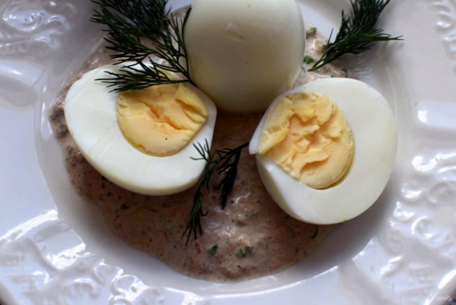 Очистите крутые яйца от скорлупы и разрежьте пополам в длину. Налейте на тарелку немного соуса и уложите яйца по 2 штуки на порцию. Полейте соусом сверху, посыпьте зеленью и украсьте розовым перцем.