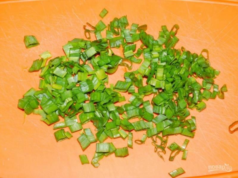 Добавьте нарезанный зеленый лук и сливки.
