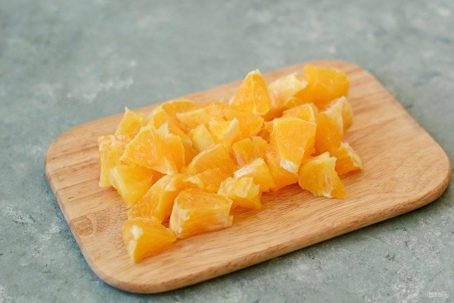 Апельсины очистите от кожуры, затем нарежьте кубиками.