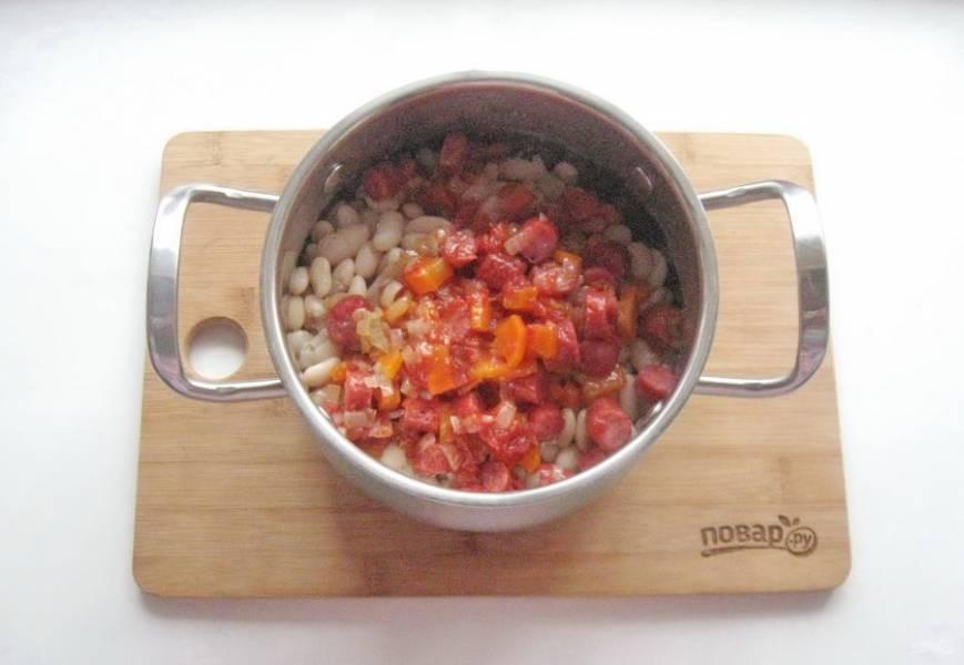 С готовой фасоли слейте воду и добавьте овощи с колбасками.