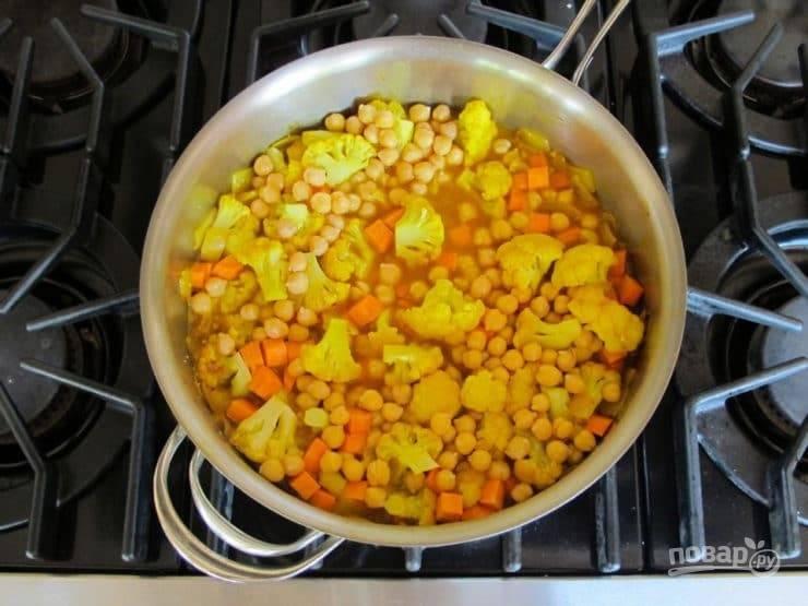4. После добавьте картофель кубиками и капусту соцветиями. Всыпьте нут. Отправьте к овощам все приправы, пасту и крахмал. Доведите продукты до кипения, а потом тушите 15 минут.