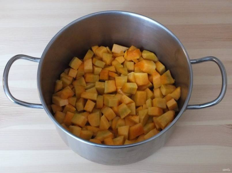 2. Тыкву очистите от кожуры и семян. Взвесьте. Чистый вес должен быть равен 500 граммам. Нарежьте кубиками толщиной 5 мм. Сложите в кастрюлю.