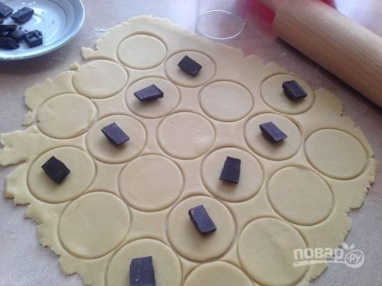 4. Раскатываем тесто в пласт толщиной 3-4 мм и вырезаем кружки. На половину кружочков выкладываем по центру кусочки шоколада.
