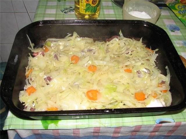 Нарезаем полукольцами морковь и лук. Капусту шинкуем, а чеснок измельчаем. Тушим овощи на сковороде (подлив немного воды) до полуготовности, посолив и поперчив по вкусу. Противень смазываем растительным маслом, выкладываем на него порезанное мясо, солим и перчим, чуть смазываем майонезом. Сверху выкладываем тушеные овощи, разровняв их по поверхности.