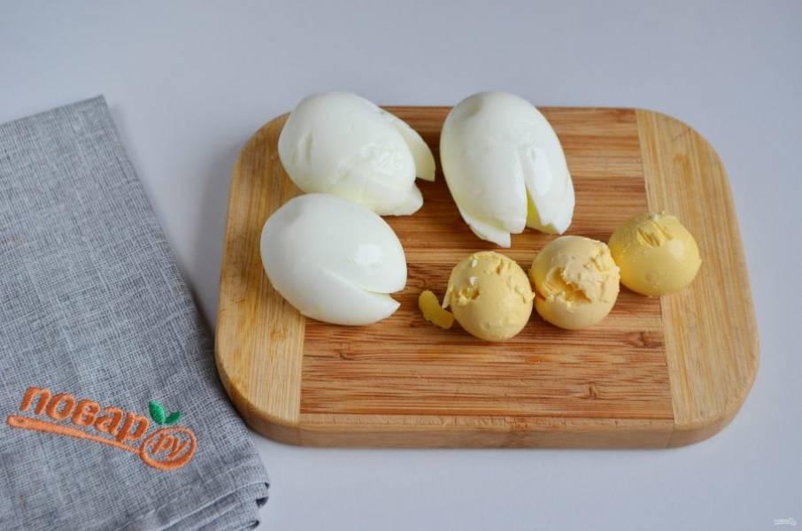 2. Надрежьте каждое яйца острым ножом крестообразно. Главное, чтобы яйцо сохранило форму, не порвалось. Осторожно извлеките желток.
