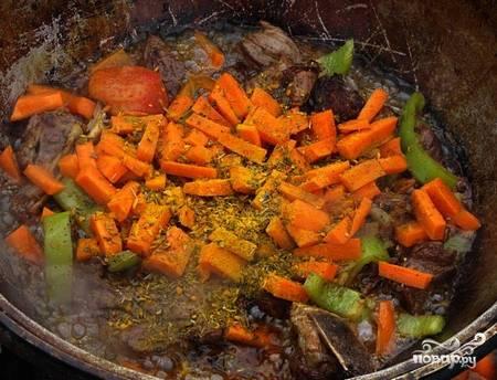 Через минутку, как перемешаем, добавляем морковь, кориандр, зиру, куркуму, соль и перец.