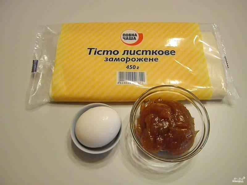 Приготовьте слоеное тесто, повидло и яйцо для смазывания рогаликов. Повидло должно быть густым, чтобы не вытекало. Тесто освободите от упаковки и разморозьте при комнатной температуре.