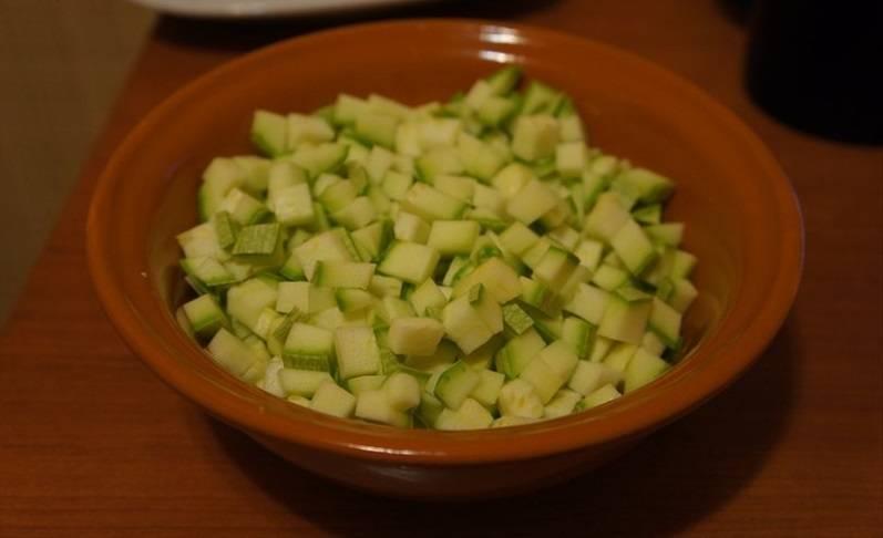 Нарежьте кубиками кабачки.
