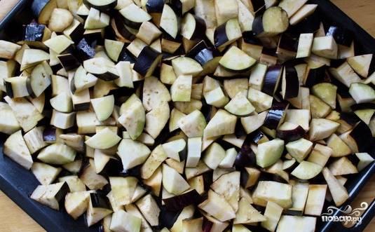 Возьмите большой противень, налейте на него немного масла. Нарезанные небольшими кусочками баклажаны выложите одним слоем и полейте небольшим количеством растительного масла. Духовку нагрейте до 200 градусов, отправьте в нее баклажаны на 30 минут. Через 15 минут от начала выпекания переверните овощи, чтобы они пропеклись равномерно.