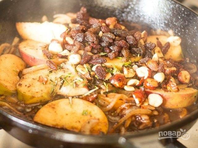 К яблокам добавьте изюм, бальзамический уксус, измельчённый розмарин и орехи. Перемешайте.