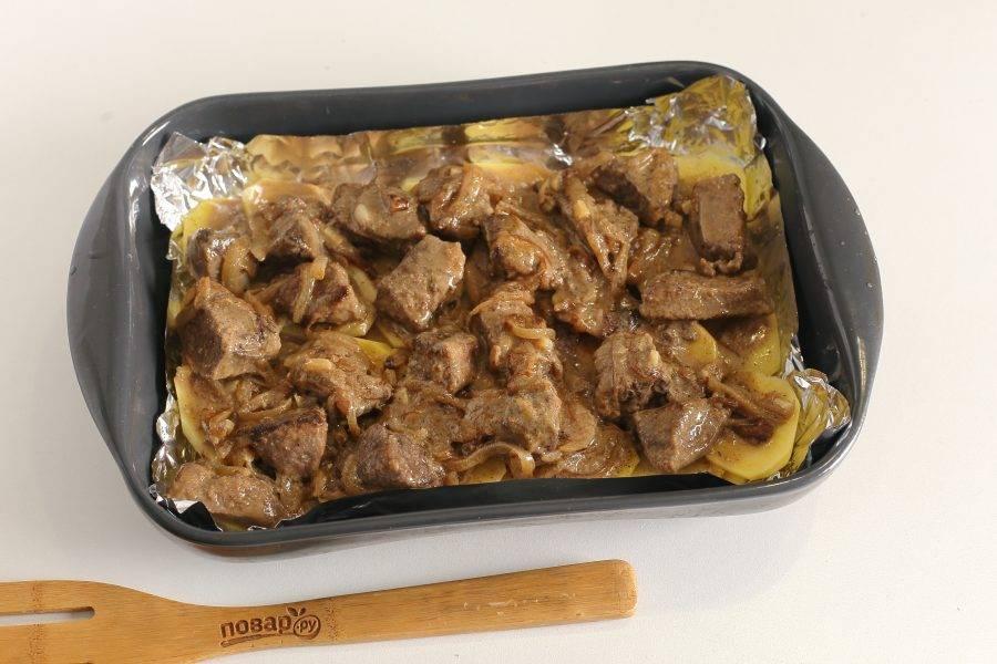Сверху картофель залейте соусом на основе сметаны вместе с кусочками печени.