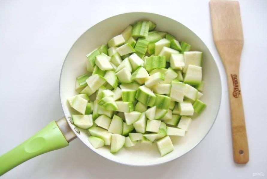 Нарежьте кабачки кубиками и выложите в сковороду.