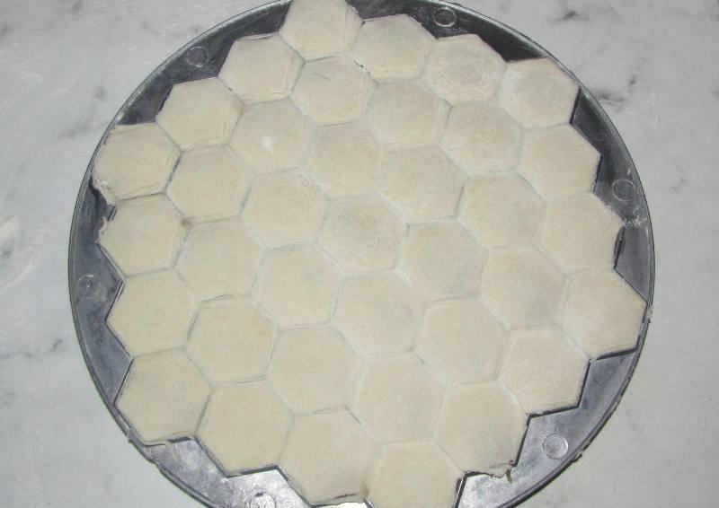 Кладем второй пласт поверх первого и при помощи скалки раскатываем все и плотно соединяем два слоя. Лишнее тесто по краям убираем.