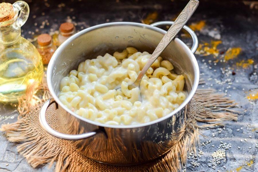 Макароны отварите практически до готовности, влейте сырно-молочный соус. Перемешайте все, посолите и поперчите.