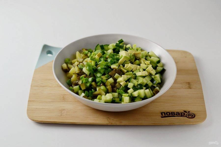 Далее добавьте в миску нарезанный кубиками авокадо и мелко порубленный зеленый лук.