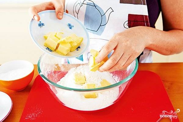 В большую стеклянную миску просейте 250 граммов муки, чтобы она насытилась кислородом. Тогда выпечка будет пышной и хорошо поднимется. Нарубите ножом сливочное масло, добавьте его к муке. Туда же всыпьте восемьдесят граммов сахарной пудры, щепотку соли, вбейте яйцо. Замесите упругое тесто, поставьте его на полчаса в холодильник.