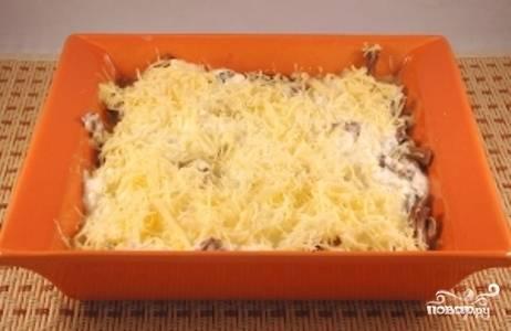 Выложите соус, и равномерно распределите его поверх грибов. Сверху посыпьте оставшимся тертым сыром.