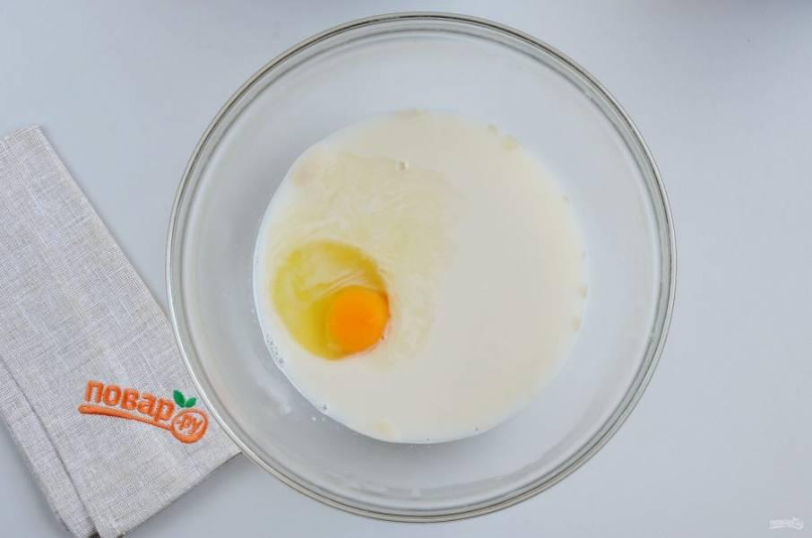 Добавьте яйцо. Половинку желтка осторожно достаньте столовой ложкой, отложите для смазывания пирога (также можно смазать молоком или белком).