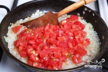 К луку добавьте помидоры и промытый рис. Тушите ингредиенты вместе в течение 6 минут на небольшом огне.