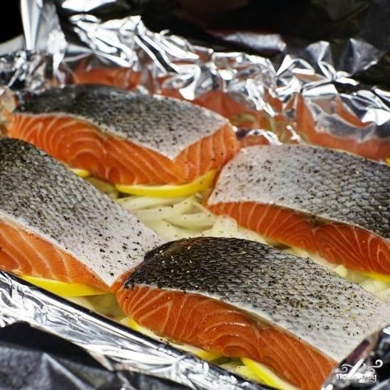 Каждый кусок лосося натираем солью и перцем, после чего выкладываем в форму.