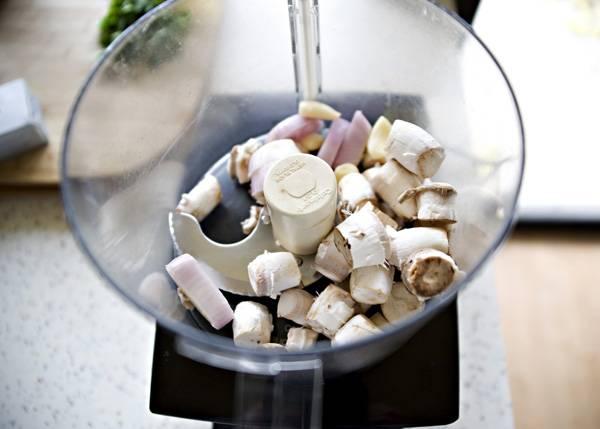 1. Грибы вымыть и как следует обсушить. Аккуратно удалить ножки и отправить их в чашу блендера. Добавить туда же очищенный лук и чеснок.