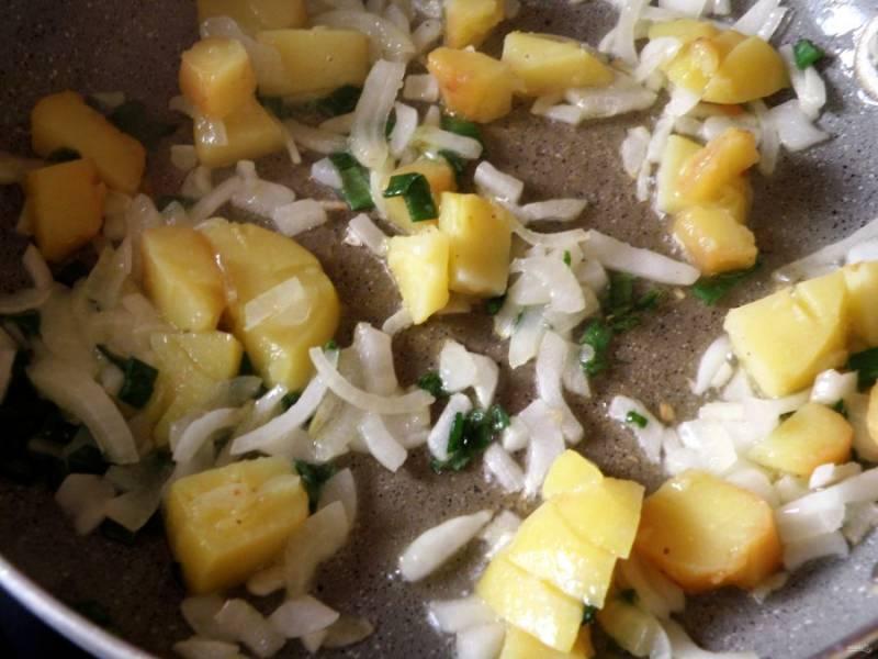 Молодой картофель сварите в мундире и остудите. Очистите или оставьте в кожуре. Нарежьте кубиками и обжарьте вместе с нарезанным зеленым луком до прозрачности лука.