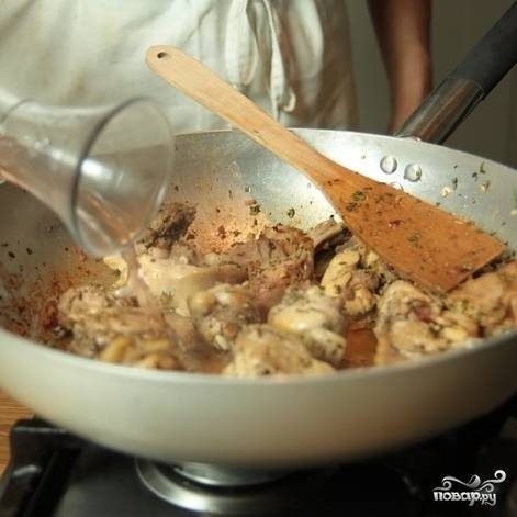 Когда кролик подрумянится, добавить вино. Когда вино выпарится, добавить бульон и готовить, пока не испарится вся жидкость (около 30 минут на медленном огне).