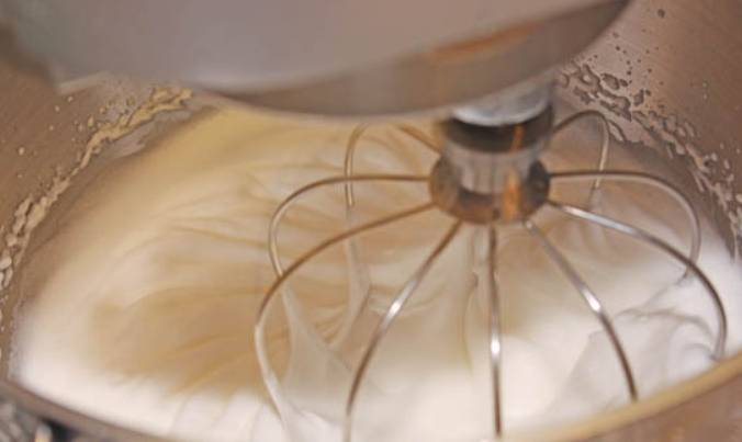 Перекладываем сухую смесь на противень, застеленный бумагой для выпечки. Ставим в духовку на 5 минут при температуре 150 градусов. После этого снова просеиваем смесь в миску, где будет замешиваться тесто. Складываем белки в кухонный комбайн, взбиваем их до устойчивой пены, постепенно добавляем сахар.