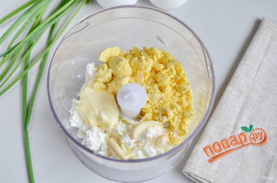 4. Маленькой ложечкой (я кофейной это делаю) извлеките желтки. Соедините их с творогом, чесноком, солью и майонезом. Не стоит добавлять майонеза больше, иначе начинка будет жидкой и не удержится внутри яйца.