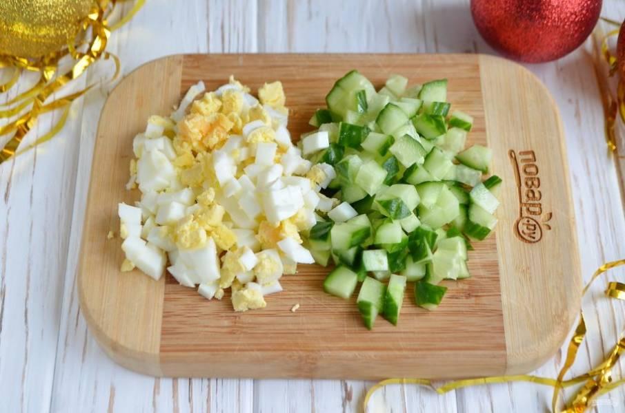 Порежьте кубиками огурец и яйца.