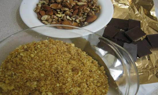 1. Подготовим ингредиенты. Шоколад ломаем на кусочки, орехи очищаем, если нужно, а печенье измельчим в крошку.