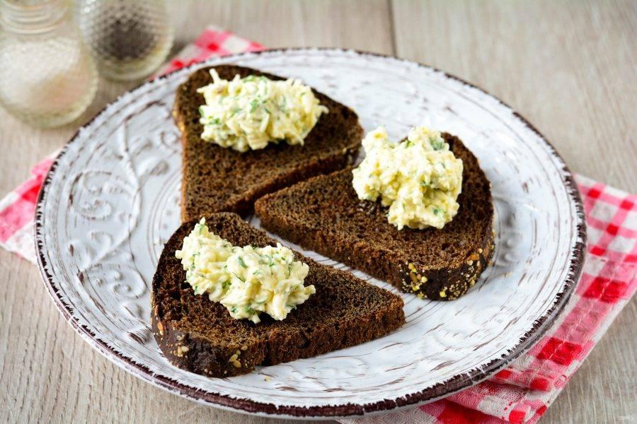 Нарежьте черный хлеб средними ломтиками. Выложите пасту на хлеб.