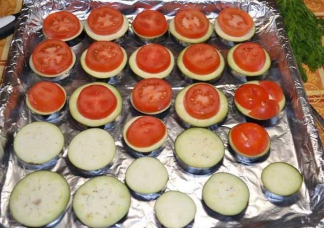 Форму для запекания застилаем фольгой и смазываем маслом. Выкладываем на нее кружочки баклажанов, сверху кладем кружочки томатов.