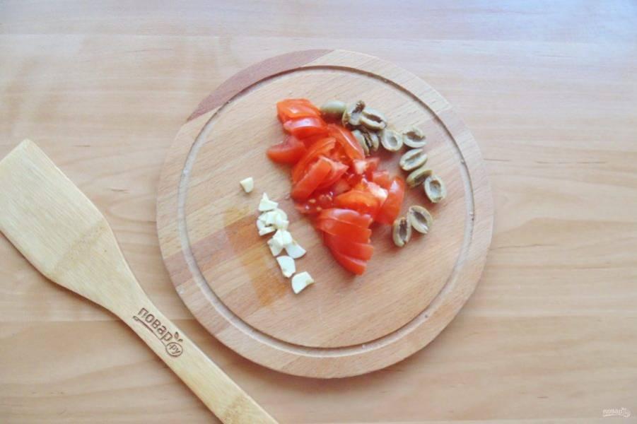 Нарежьте помидор, оливки и чеснок.