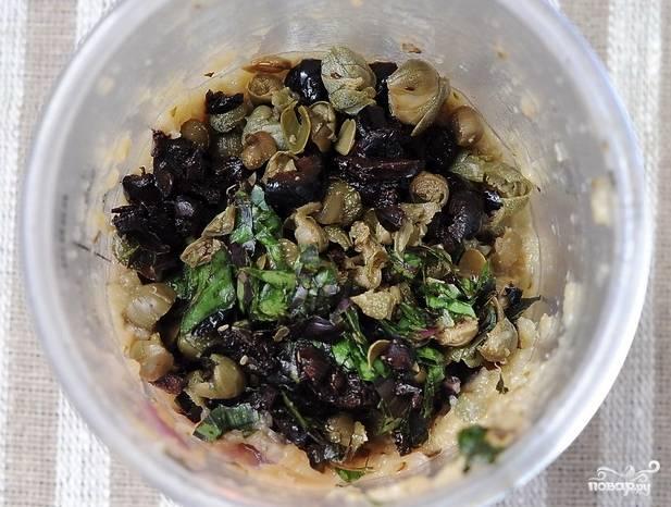 После запекания остудите баклажан, достаьте из него мякоть и положите её в блендер вместе с луком и чесноком. Туда же отправьте каперсы, оливки, базилик. Измельчите всё до однородной массы.