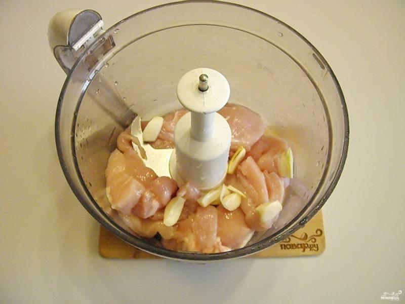 Вымойте куриное филе и порежьте крупными кусками. очистите чеснок. Сложите мясо и чеснок в чашу блендера и измельчите.