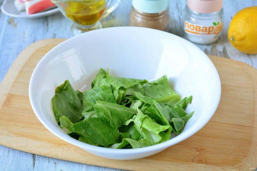 Порвите руками салатные листья и выложите в миску.