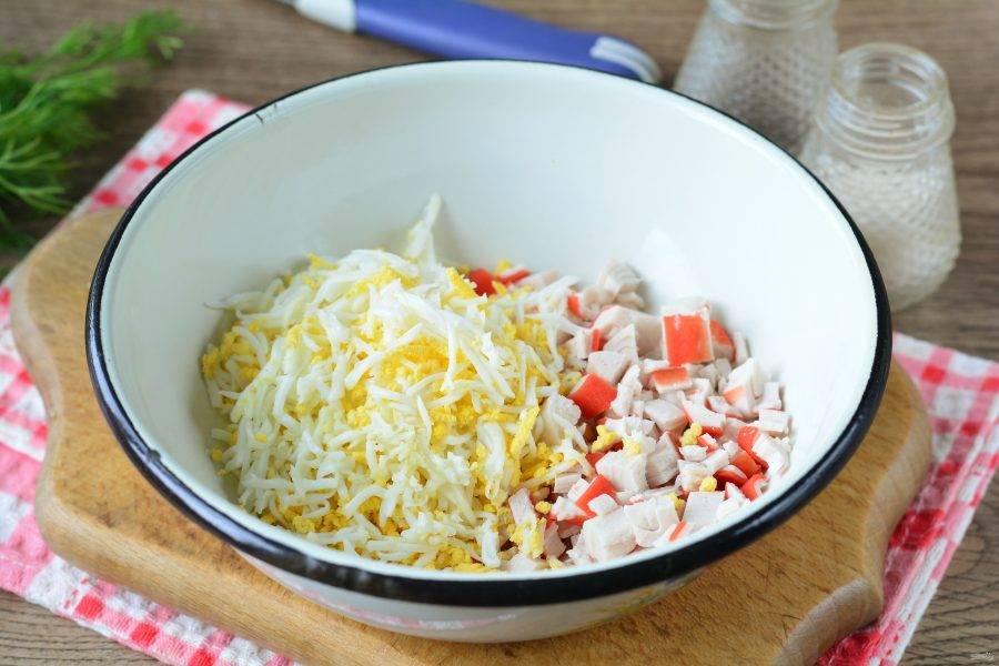 Всыпьте в миску крабовые палочки и натертые яйца.