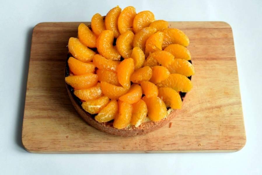 Достаньте пирог и украсьте его сверху мандаринами, предварительно очистив их и убрав все пленочки. Можно воспользоваться консервированными мандаринами в сиропе, предварительно слив его. На основе сиропа можно приготовить желе и залить пирог сверху.