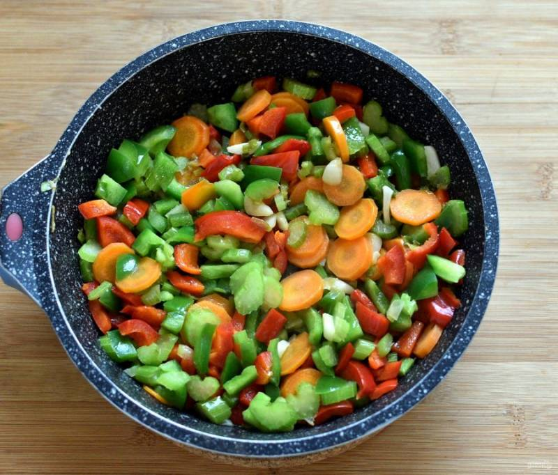 Затем выложите в сковороду морковь, сельдерей и перец. Пассеруйте 3-4 минуты.